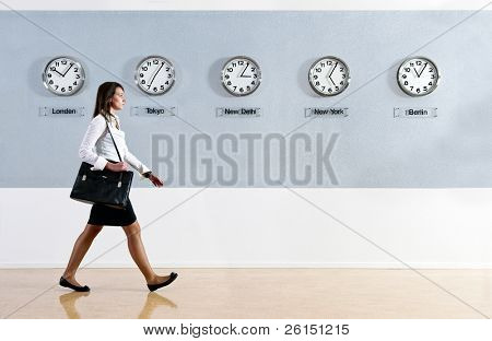 Business woman walking in a hurry past a row of clocks showing the time in various parts of the world. Business, travel, time concept