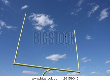 Football uprights with a ball kicked through