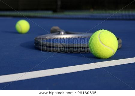 Tennis balls on the court with a racket