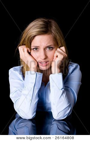 very sad, unhappy and upset woman in blue shirt, studio shoot isolated on black