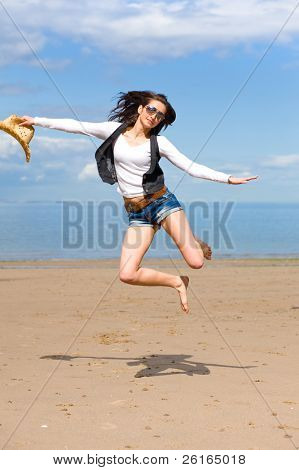 young attractive female jump high over sandy summer, wears sunglasses and hold straw hat in her hand