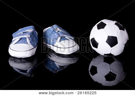 pair of small baby shoes next to football ball, footballer baby or baby footballer concept, studio shoot isolated on black with reflection