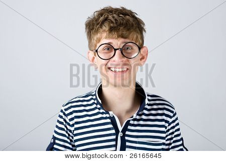 young student, male in glasses, confused, surprised, studio shoot isolated on grey background