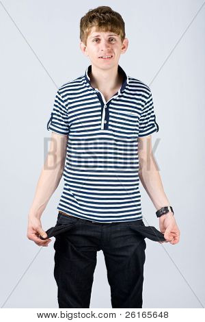 stressed moneyless student shows empty pockets, studio shoot isolated on grey background