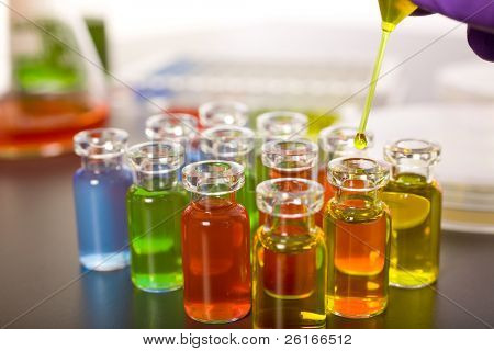 laboratory colorful test tubes, pipette with yellow fluid over one of the bottles, science, experiment
