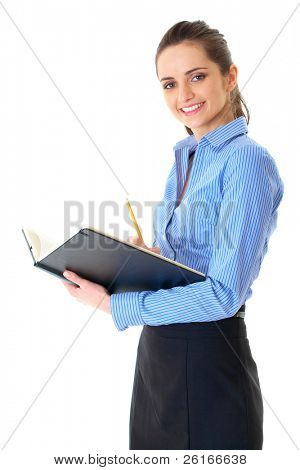 young happy female in blue shirt makes some notes in notepad, isolated on white