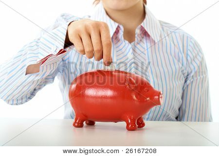 redhead girl puts coin into red piggy bank, savings concept, isolated on white background