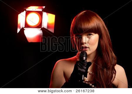 young female singer holds microphone, red stage light at background, isolated on black