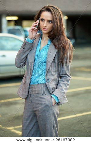 young very attractive female talks over her mobile phone, blurred car park as background, outdoor shoot