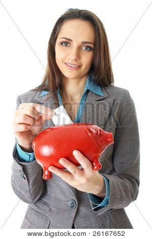 young attractive female puts 20 pound note into red piggy bank, isolated on white