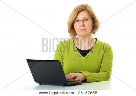 mature woman in green top and glasses works on her netbook, isolated on white