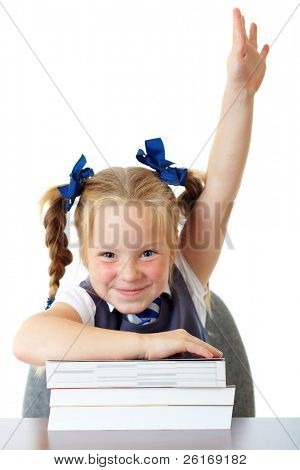 Blonde happy schoolgirl in blue dress and matching tie rises her hand up, while sitting at school desk with pile of books, isolated on white