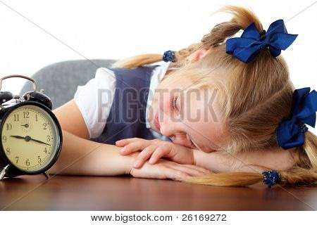 Young cute schoolgirl sleeps at her desk, tired, overworked, isolated on white