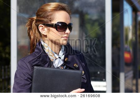 Attractive and trendy businesswoman wait for bus, outdoor shoot