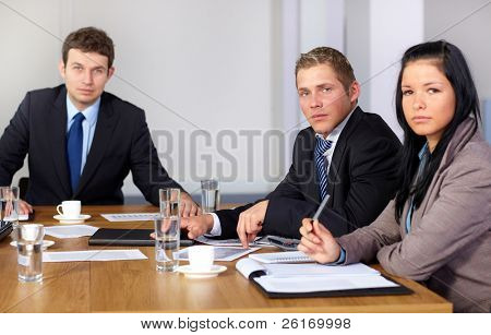 Team of 3 business people during meeting, sitting at big conference table