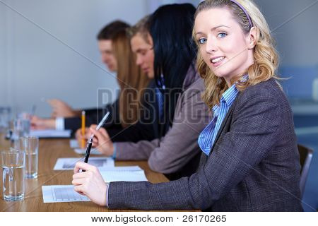 Portrait of young attractive blonde businesswoman sitting at conference table with 4 other colleagues, all work on some documents and she looks to camera