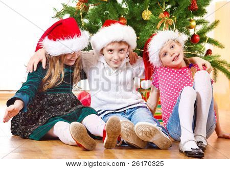 Group of preschool kids beside Christmas tree