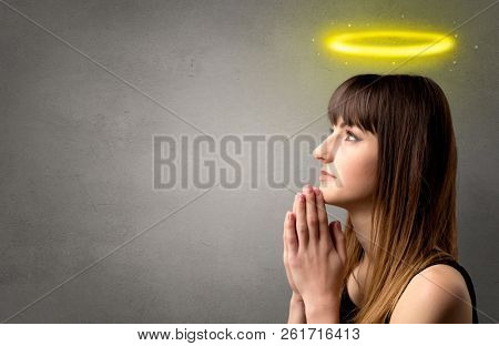 poster of Young woman praying on a grey background with a shiny yellow halo above her head