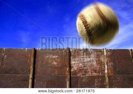 Baseball flying through the air with clouds sky and fence in background