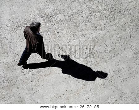 Man walking on sidewalk with black shadow