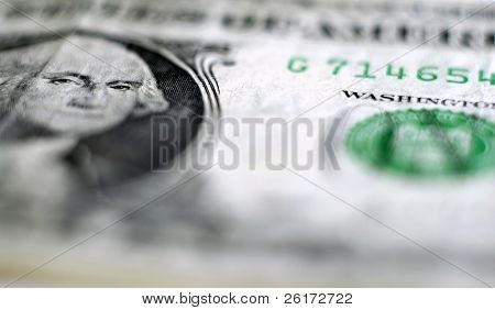 Closeup of one dollar bill focused on George Washington's face