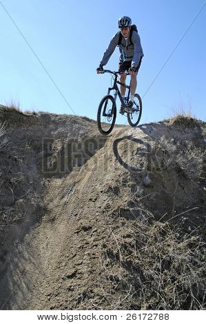 Man mountain biking on trail in outdoors