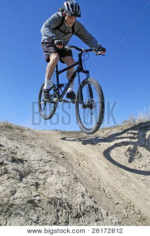 Man mountain biking on trail in outdoors