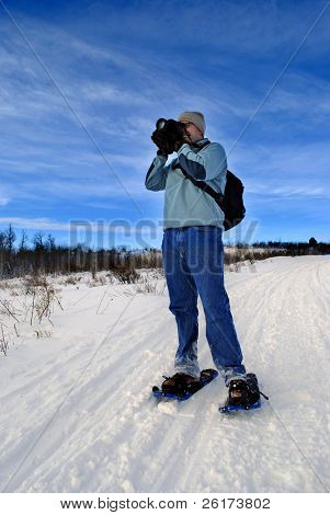 Snowshoeing Photographer in White Snow with Snowshoes