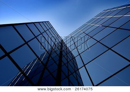 Office building details reflecting blue sky in windows