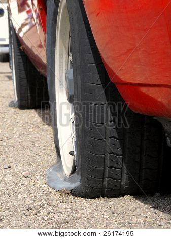 Car with two flat tires on roadside