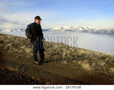 Eine Person gehen mit Tal und Nebel mit Bergen im Hintergrund