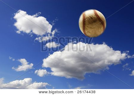 Baseball flying through the air with clouds and sky in background