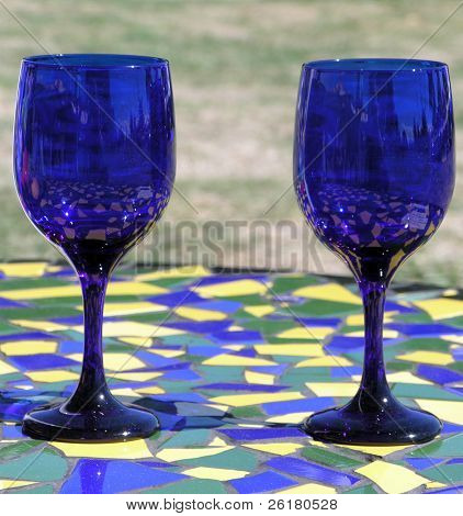 Two blue wine glasses on a mosaic tiled table