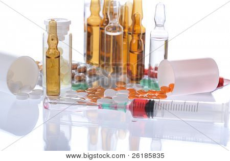 colorful pills, ampules, syringe on white background