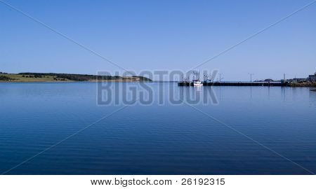 Boats moored at the docks on calm ocean waters in early morning light; Cape Breton, NS, Canada