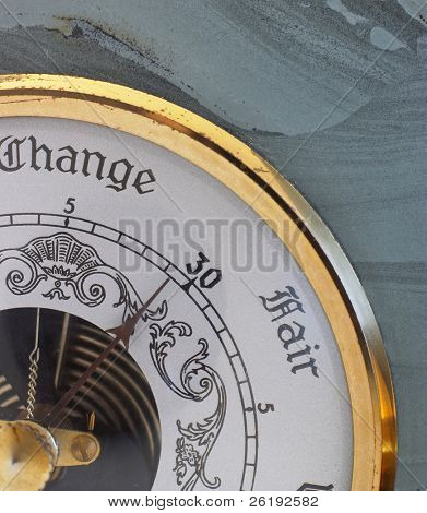 A barometer, set in a block of volcanic ash, with its needle hovering between 'change' and 'fair'