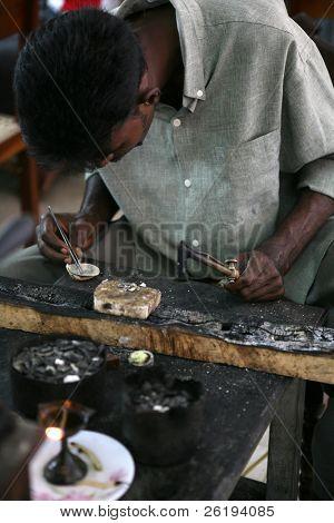 A Sri Lankan goldsmith smelting jewellery