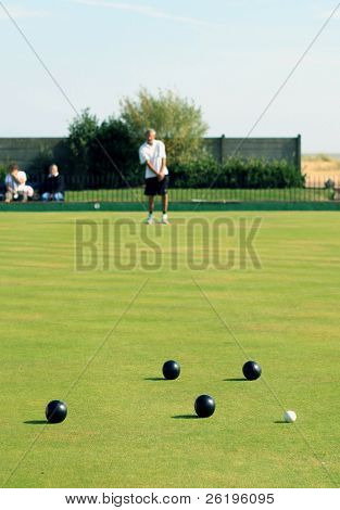 A bowler playing on the village green. Bowls is a traditional British game. The faces of the bowler and the spectators are unrecognisable, as the shallow focus is on the balls.