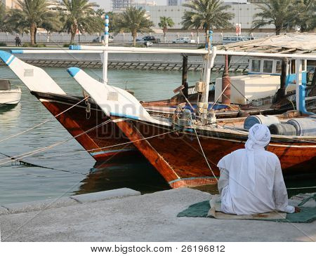 A fisherman sits beside his dhow in Doha, Qatar, during the heat of the day. September 2008 (Ramadan)