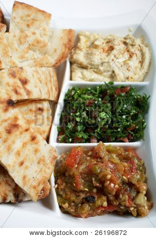 Traditional Arab or Mediterranean mezze with Turkish flat bread. From the front: babaganoush, tabouleh and hummus
