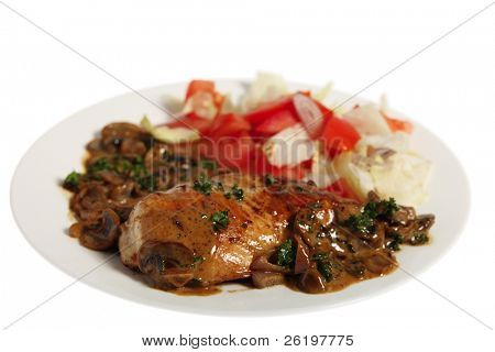 A fried chicken breast topped with mushrooms in a creamy sauce and served with a salad, isolated on white.