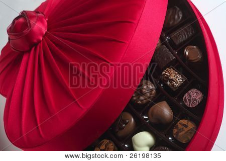 An open red heart-shaped box of luxury chocolates