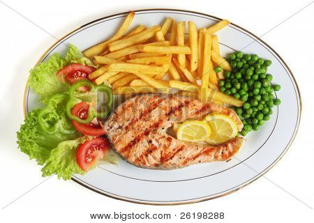 A view of a grilled salmon steak meal served with salad, chips, peas and lemon slices.