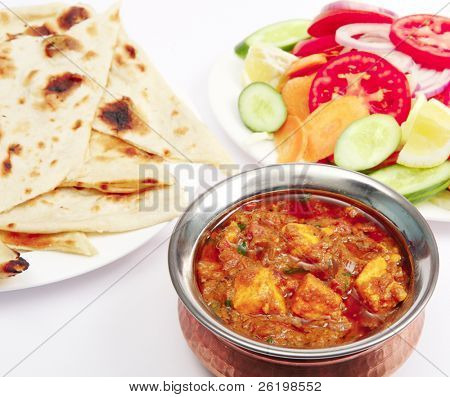 A bowl of kadai paneer (cheese) curry with naan bread and a side salad.