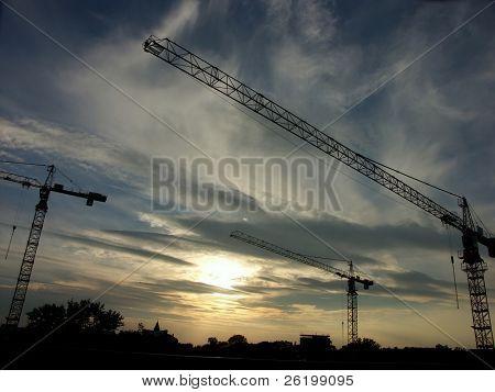 Jib cranes against the sun setting