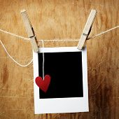 image of clotheslines  - Blank instant photo and small red paper heart hanging on the clothesline - JPG