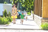 Mom And Child Are Walking Along The Street. A Woman And Her Son Are Walking Around The City. The Boy poster
