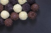 Delicious Chocolate Truffles On Black Stone Background. Assortment Of Fine Chocolates In White Dark  poster