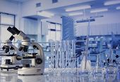 Modern scientific laboratory interior. Laboratory glassware and microscope on the glass table. poster