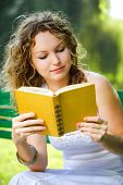 stock photo of girl reading book  - Beauty woman reading a book in park - JPG